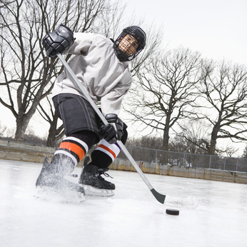 Boy in ice hockey uniform skating on ice rink moving puck.